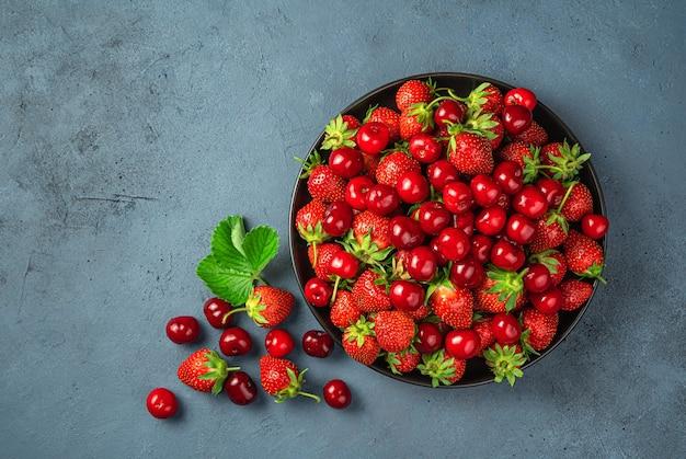 Frutta fresca e bacche estive su uno sfondo scuro. succose ciliegie e fragole in un piatto nero.