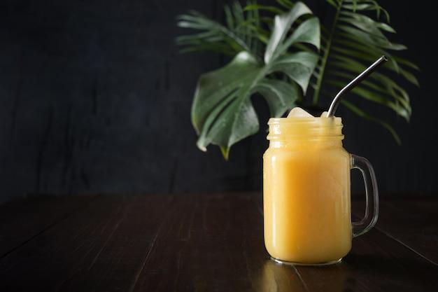 Frullati di frutta fresca estate con banana, lime sul tavolo di legno tropicale scuro. avvicinamento.