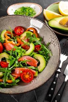 Insalata di verdure fresche estive con rucola, pomodori, peperoni, avocado e salmone su un piatto vicino alla foto verticale.
