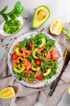 Insalata di verdure fresche estive con rucola, pomodori, peperoni, avocado e salmone su una foto verticale di vista dall'alto del piatto.