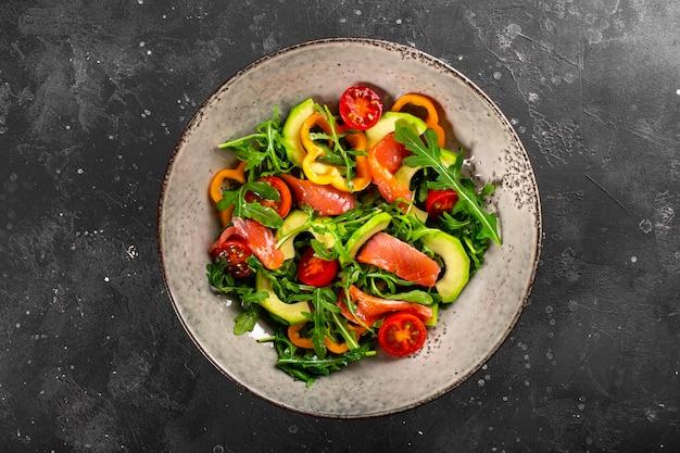Insalata di verdure fresche estive con rucola, pomodori, peperoni, avocado e salmone su una vista dall'alto del piatto.