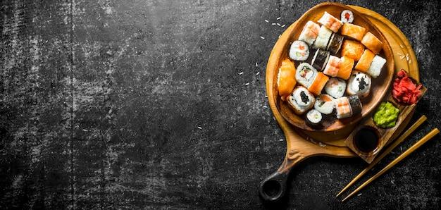 Rotoli di sushi freschi in un piatto su un tagliere con bacchette e salse. sul tavolo rustico scuro