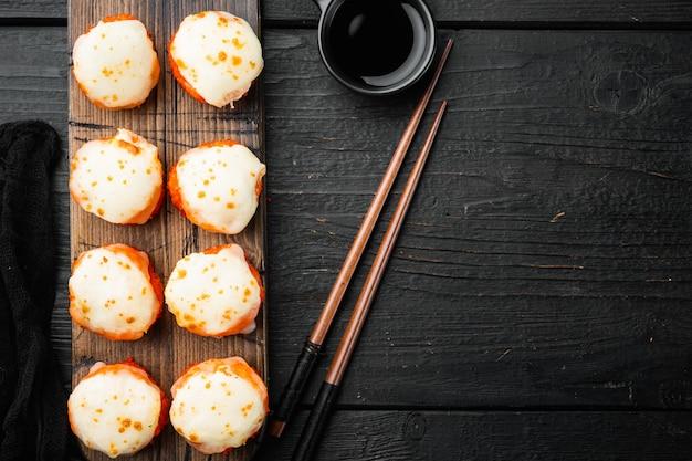 Rotoli di sushi freschi con wasabi e set di zenzero, su tavolo di legno nero