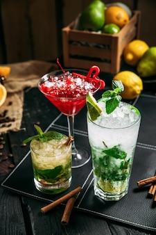 Cocktail dolci freschi dell'alcool in vetri differenti, mojito cosmopolita e mai tai sui precedenti di legno scuri, primo piano, verticale