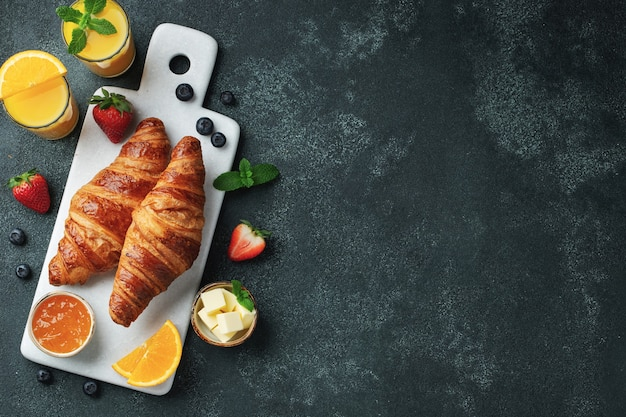 Croissant dolci freschi con burro e marmellata di arance per colazione. colazione continentale su uno sfondo di cemento scuro. vista dall'alto con copia spazio. disposizione piatta.