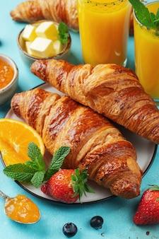Croissant dolci freschi con burro e marmellata di arance per colazione.