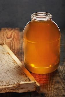Miele dolce fresco in un grande barattolo di vetro su una tavola di legno