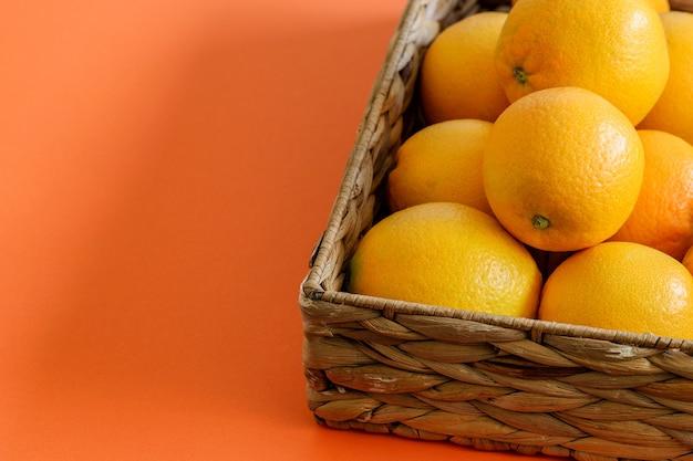 Arance dolci fresche nel cestino rustico sullo sfondo corallo. frutta e dieta vegetale.