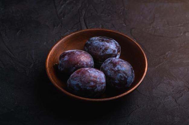 Frutti di prugne dolci freschi in ciotola di legno marrone, tavola strutturata nera, vista di angolo