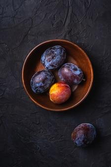Frutti di prugna dolce freschi in ciotola di legno marrone, tavolo testurizzato nero, vista dall'alto