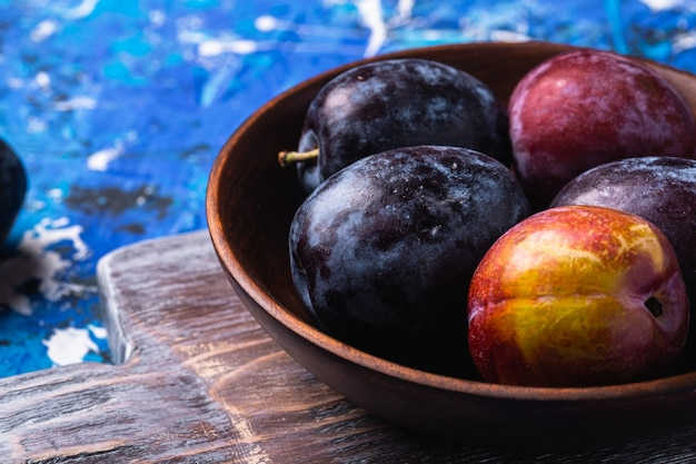 Frutti di prugna dolce freschi in ciotola di legno marrone sul vecchio tagliere, tavola astratta blu, macro di vista di angolo