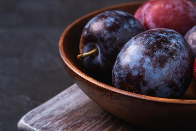 Frutti di prugna dolce freschi in ciotola di legno marrone sul vecchio tagliere