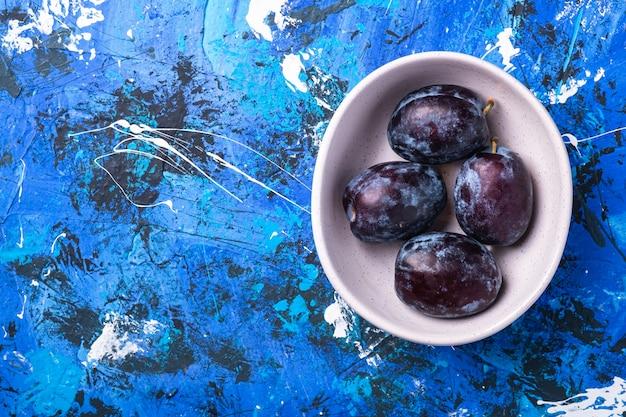 Frutti di prugna dolce freschi in ciotola bianca su fondo astratto blu, spazio della copia di vista superiore