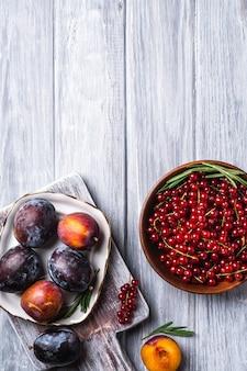 Dolce fresco prugna frutti interi e tagliati a fette nella piastra con foglie di rosmarino sul vecchio tagliere con bacche di ribes rosso nella ciotola di legno