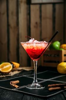Cocktail cosmopolita rosso dolce fresco in vetro con ghiaccio tritato sui precedenti di legno scuri, vista laterale
