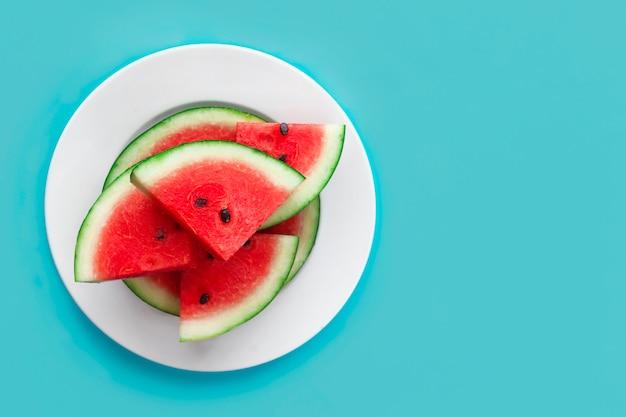 Fette dolci fresche di anguria rossa matura sul piatto bianco sul blu. vista dall'alto, piatto. copia spazio, posto per il testo. cibo crudo sano per vegan, vegetariani, concetto di vacanze estive. tagliare la frutta