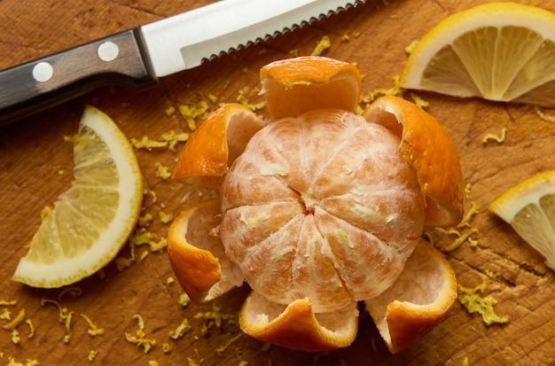 Mandarino fresco frutta e fette di limone su una tavola di legno