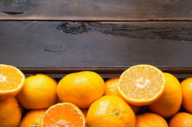 Mandarini freschi in scatola marrone su fondo in legno
