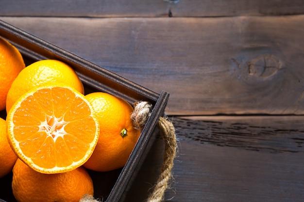 Mandarini freschi in scatola marrone su legno