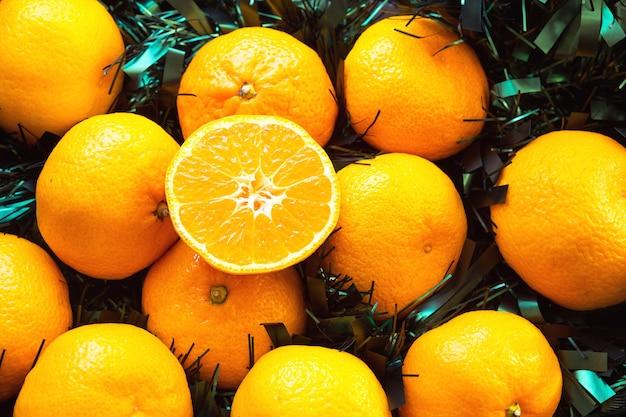 Mandarini freschi a luci ghirlande, su rami di abete e orpelli