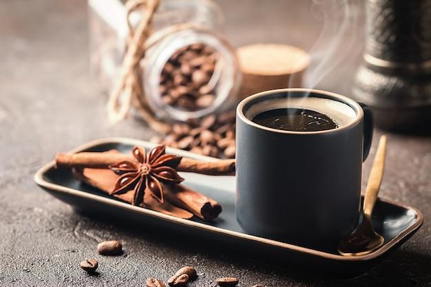 Tazza di caffè espresso nero gustoso fresco di caffè caldo con cannella, stelle di anice e chicchi di caffè su sfondo scuro