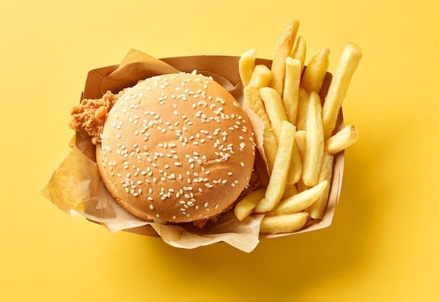 Hamburger fresco e gustoso e patate fritte su sfondo di carta gialla, vista dall'alto