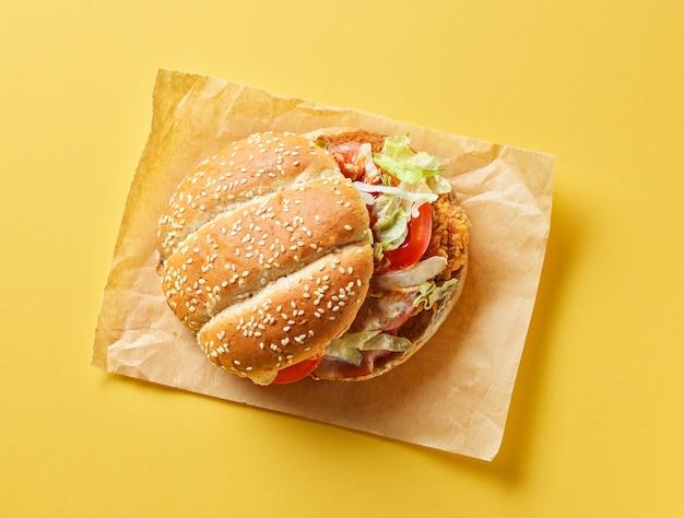 Hamburger fresco e gustoso su sfondo di carta gialla, vista dall'alto