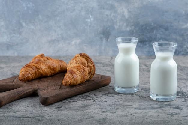 Croissant freschi e gustosi con brocche in vetro di latte poste sul tavolo in pietra.