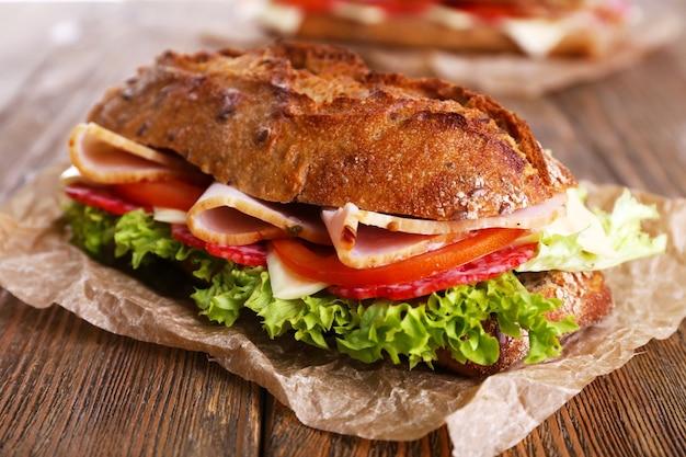 Panini freschi e gustosi con prosciutto e verdure su fondo in legno