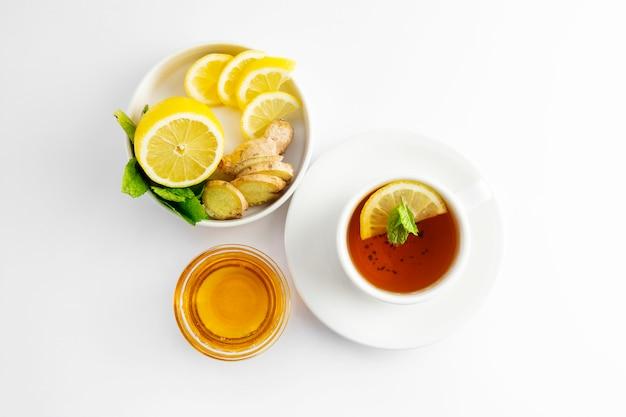 Tè fresco con limone e miele su un bianco. tazza di tè calda isolata, disposizione piana di vista superiore. disteso. bevanda autunnale, autunnale o invernale. copyspace.
