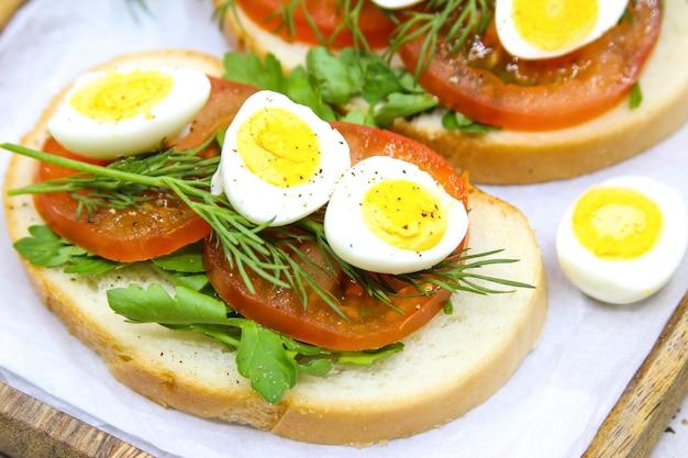 Toast freschi con uova di quaglia pomodori ed erbe verdi primo piano vista dall'alto da vicino