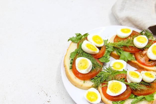 Panini tostati freschi con uova di quaglia pomodori ed erbe verdi closeup vista dall'alto spazio copia