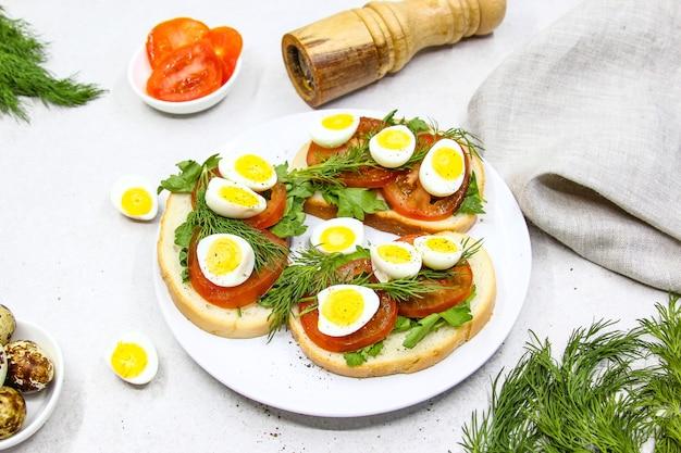 Toast freschi con uova di quaglia pomodori e primo piano di erbe verdi vista dall'alto
