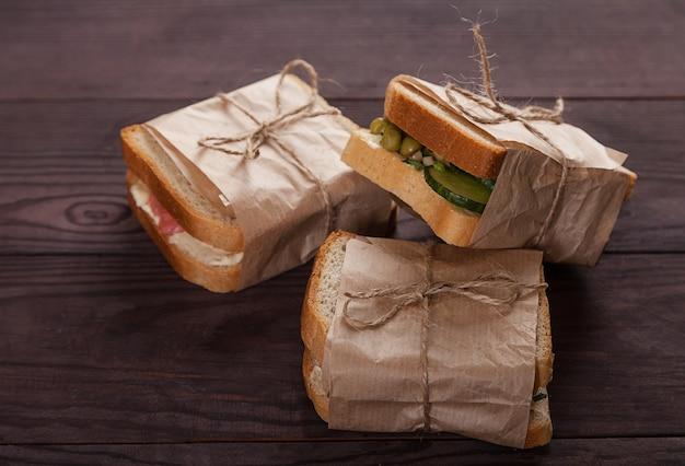 Pane tostato fresco con salmone, crema di formaggio e verdure giacciono in una pila, avvolti in carta artigianale.
