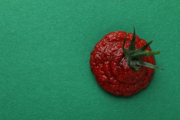 Concentrato di pomodoro fresco sulla superficie verde, spazio per il testo