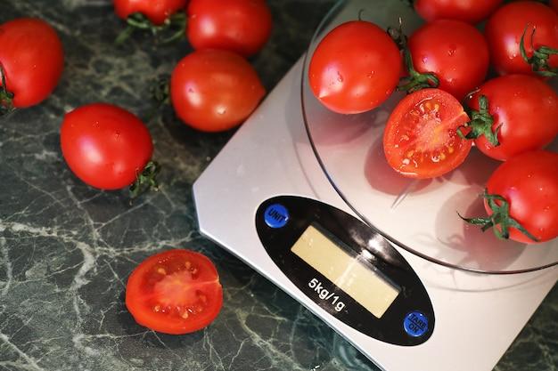 Pomodori freschi sulla bilancia da cucina pesando e misurando