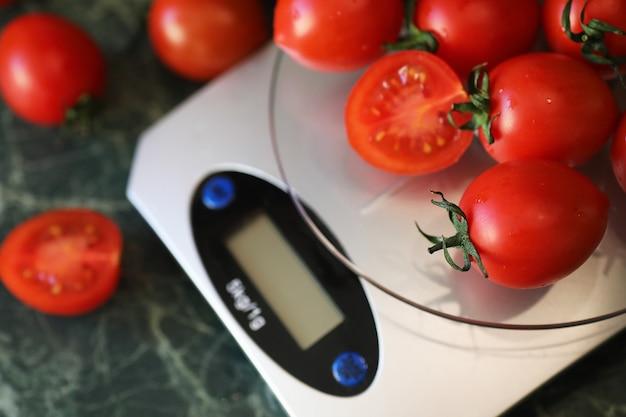Pomodori freschi su bilancia da cucina pesatura e misurazione