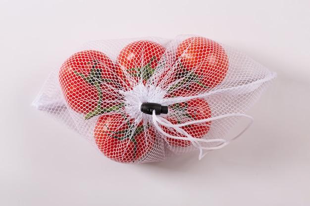 Pomodori freschi in rete di imballaggio riutilizzabile isolato su sfondo bianco