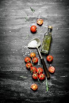 Pomodori freschi con olio d'oliva e un cucchiaio di sale. su sfondo nero rustico.
