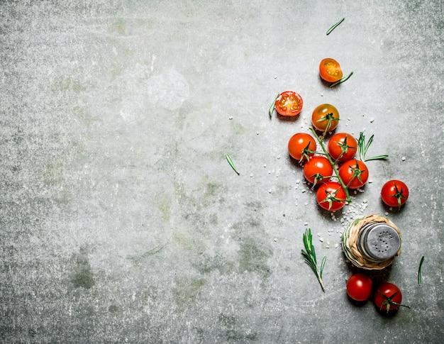 Pomodori freschi con sale e rosmarino. su un tavolo di pietra.