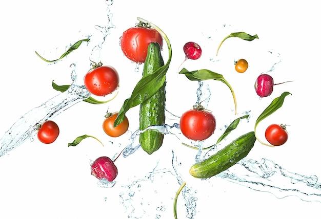I pomodori freschi, cetrioli, ravanelli in spruzzi d'acqua isolati su bianco.