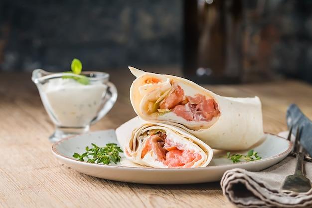 Involucro di tortilla fresca con verdure e salmone sul piatto