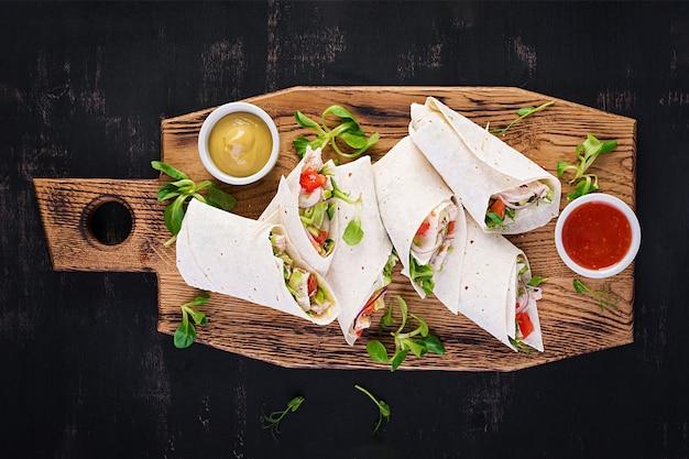 Impacchi di tortilla fresca con pollo e verdure fresche su tavola di legno.