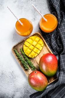 Succo di mango di frullato di frutta tropicale fresca e mango fresco. sfondo grigio. vista dall'alto