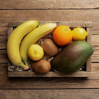 Frutta tropicale fresca in una scatola di consegna in legno su un tavolo di legno. arancia, banana, mango, kiwi e limone, vista dall'alto.