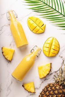 Frullato tropicale fresco con ananas e mango in bottiglie su marmo