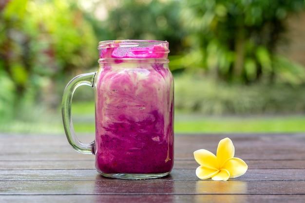 Frullato tropicale fresco con frutta drago rosso, avocado verde, yogurt e miele in tazza di vetro per colazione, primi piani