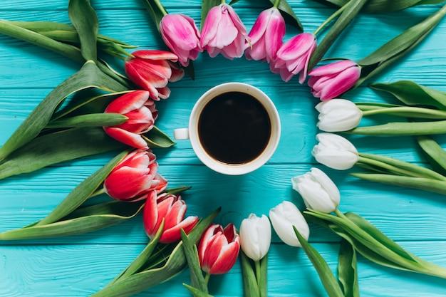 Tulipani freschi intorno a una tazza di caffè. concetto di giorno di madri, vista dall'alto.