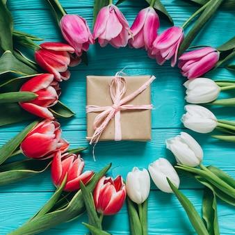 Tulipani freschi intorno a un regalo. concetto di giorno di madri, vista dall'alto.