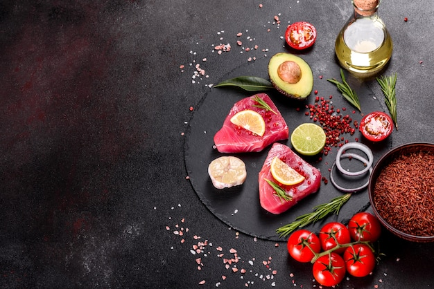 Bistecche di filetto di tonno fresco con spezie ed erbe aromatiche su sfondo nero.